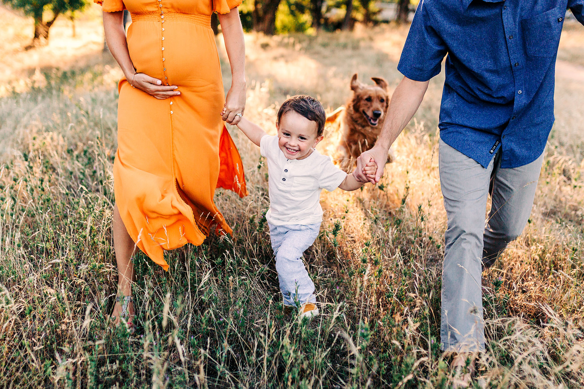 A family of three runs and plays together during lifestyle maternity portraits with photographer Amy Wright in Roseville, California.