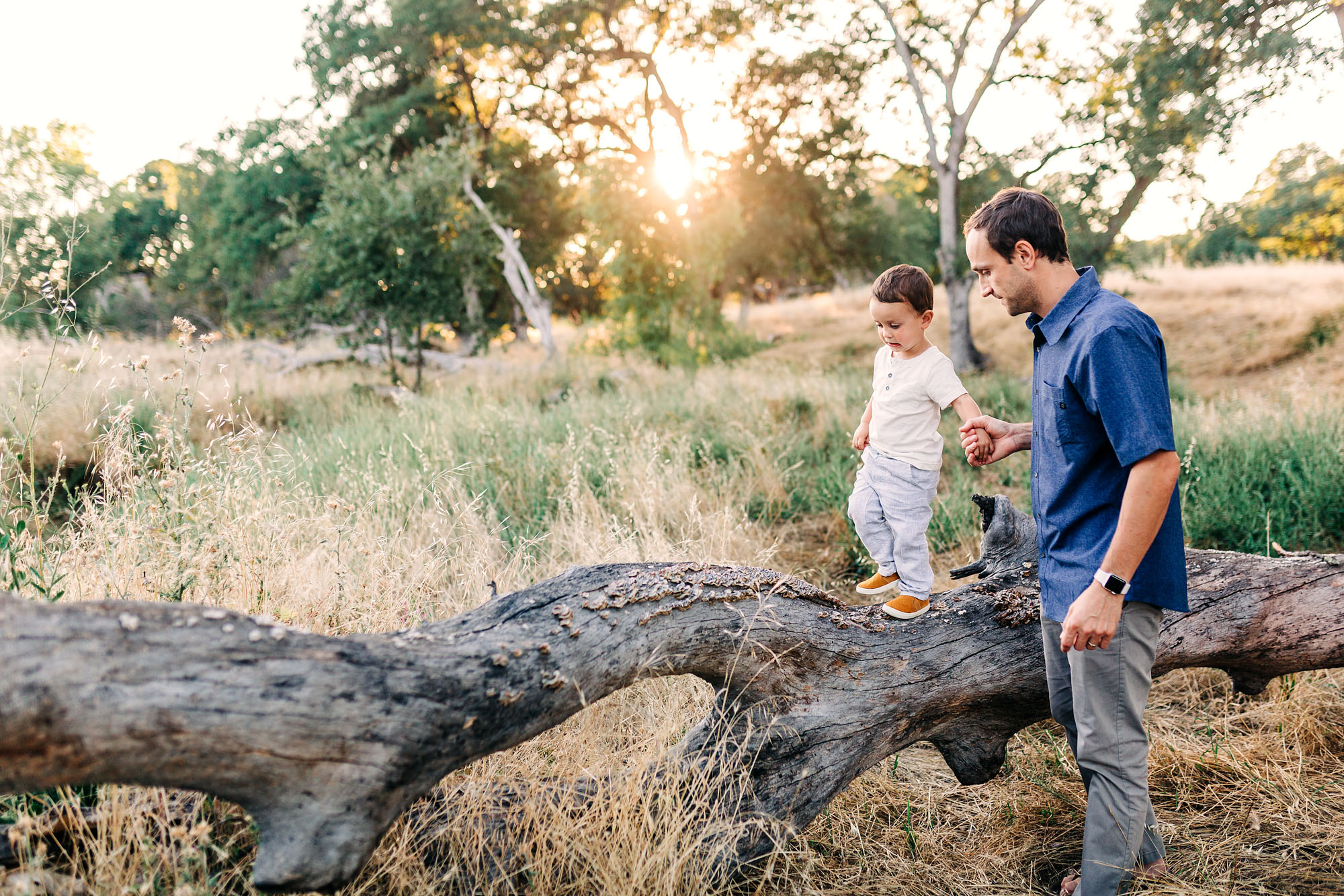 A father helps his sun as they play together during family pictures with lifestyle photographer AMy Wright in Roseville, California.