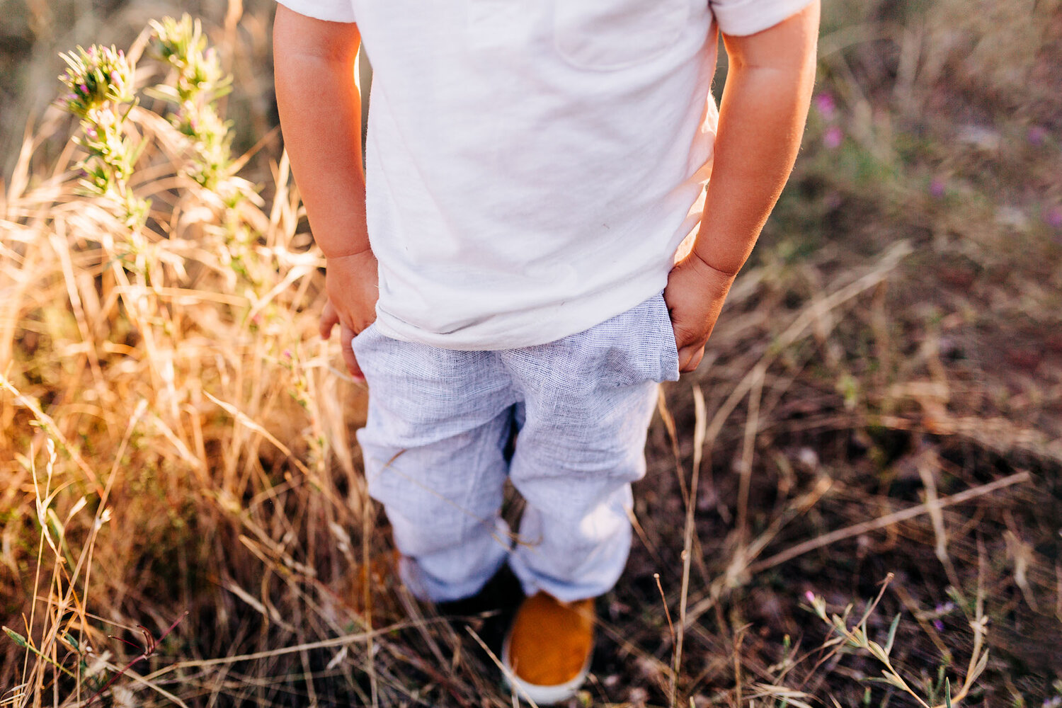 A toddler tucks his hands in his pockets during a photo session with Roseville family photographer Amy Wright.