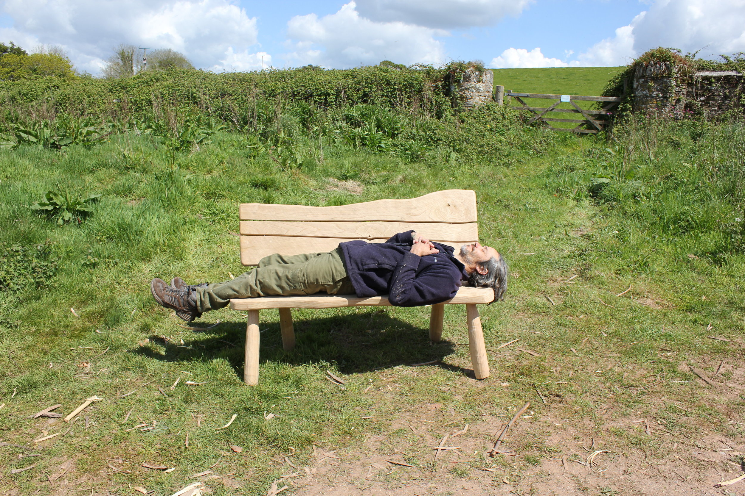 Richard enjoying a well-earned 5 minute nap on his sweet chestnut slab backed bench. This is a prototype for future benches at Rame Head woods.