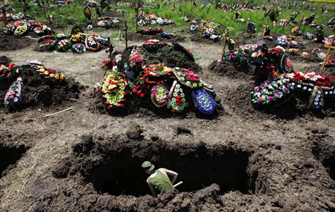 A soldier digs a grave outside Krymsk, Russia. More than 170 residents of the town died in early morning floods Sunday July 8.
