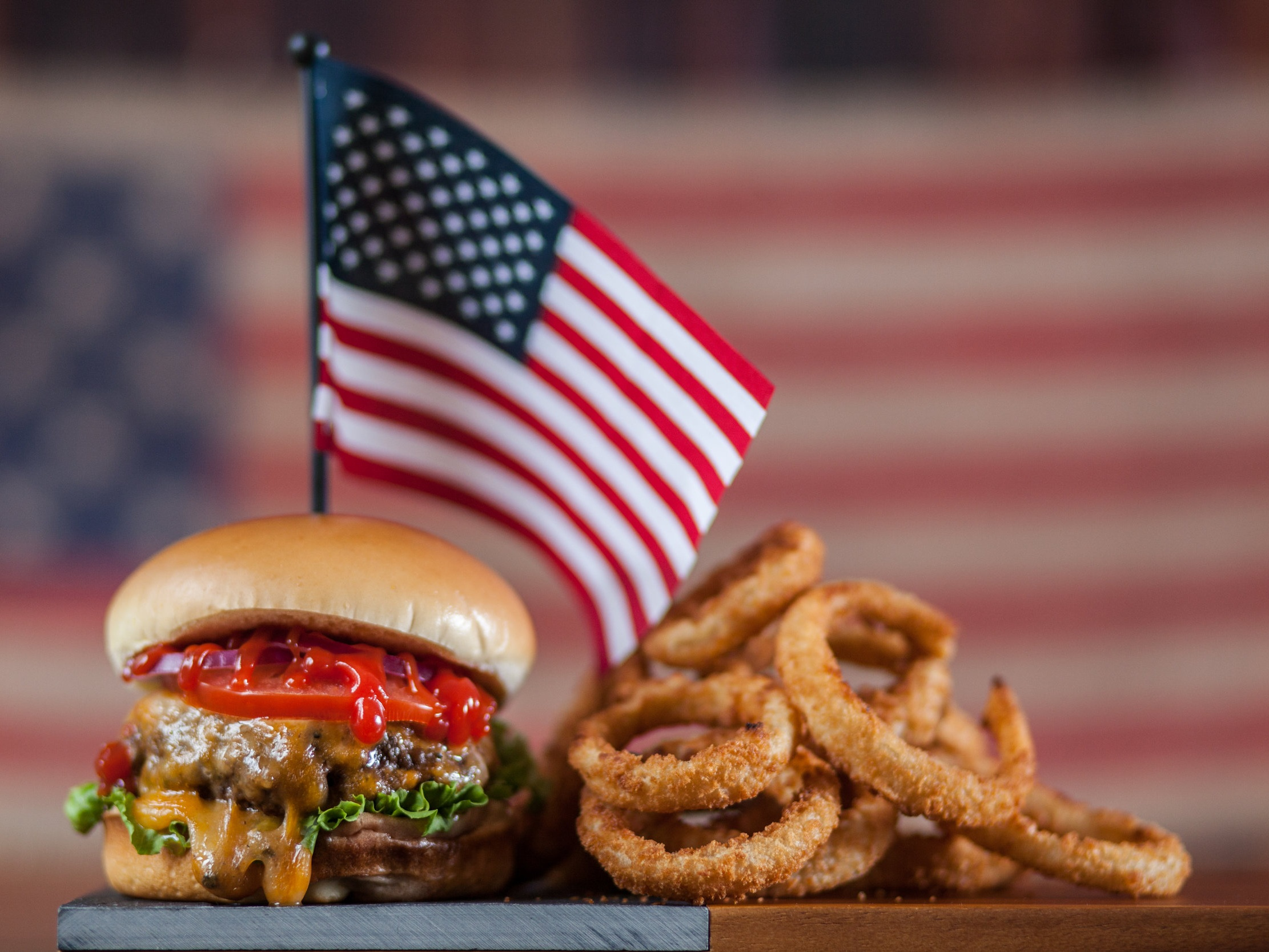 All-American Burger - The All-American burger gets you right in that sweet nostalgia spot for summers of youth and whatnot. Classic and perfect, with onions, pickles, tomatoes, and cheddar cheese. Perhaps the perfect burger for holiday salutations.