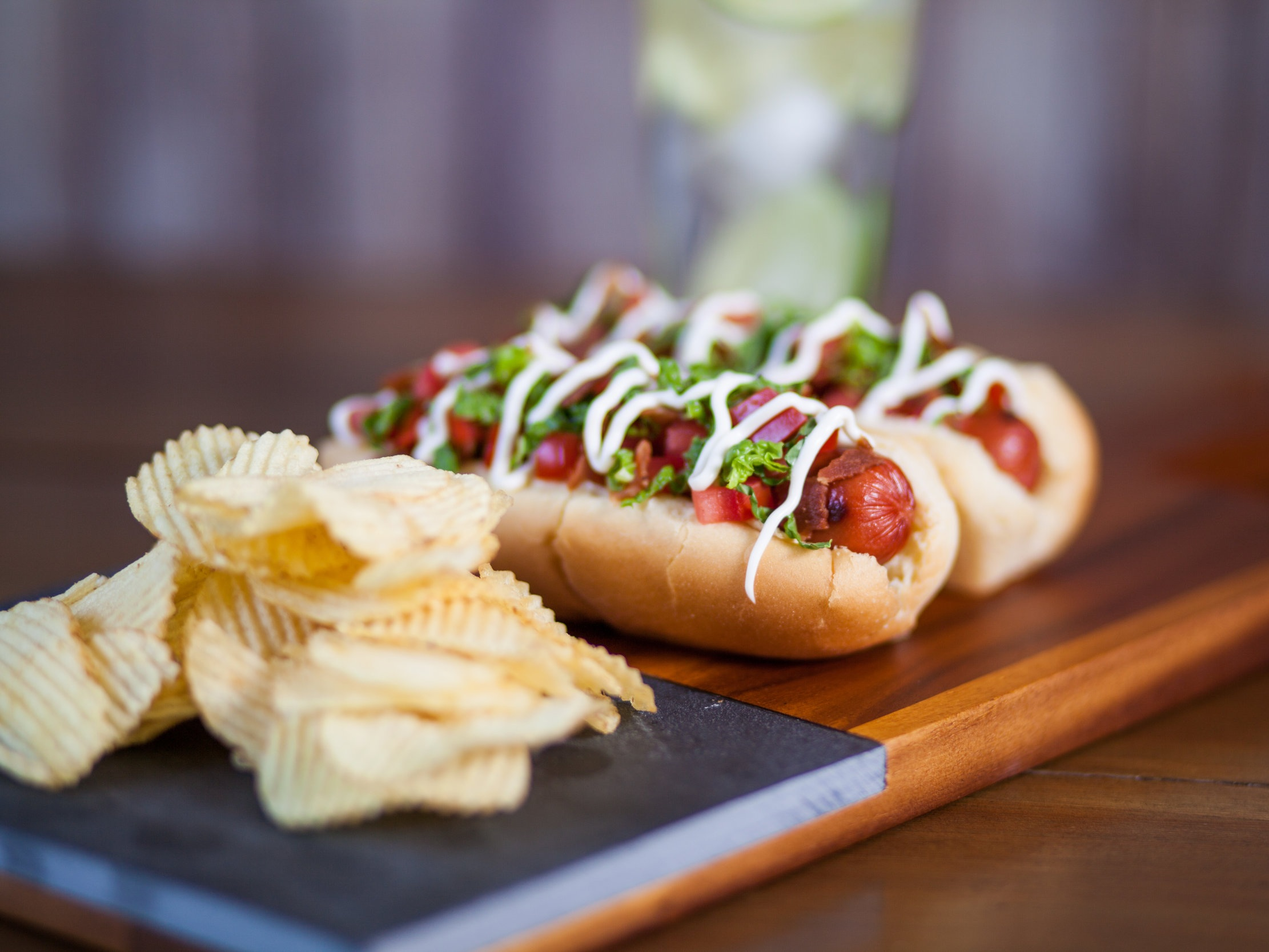 BLT Hot Dog - Sometimes it's hard work to choose between a sandwich and a hot dog. Why choose? This BLT Hot Dog incorporates the best parts of a BLT with a hot dog for a truly satisfying experience. On our Hearth White Hot Dog buns layer bacon, chopped tomatoes, lettuce and mayonnaise and relax!