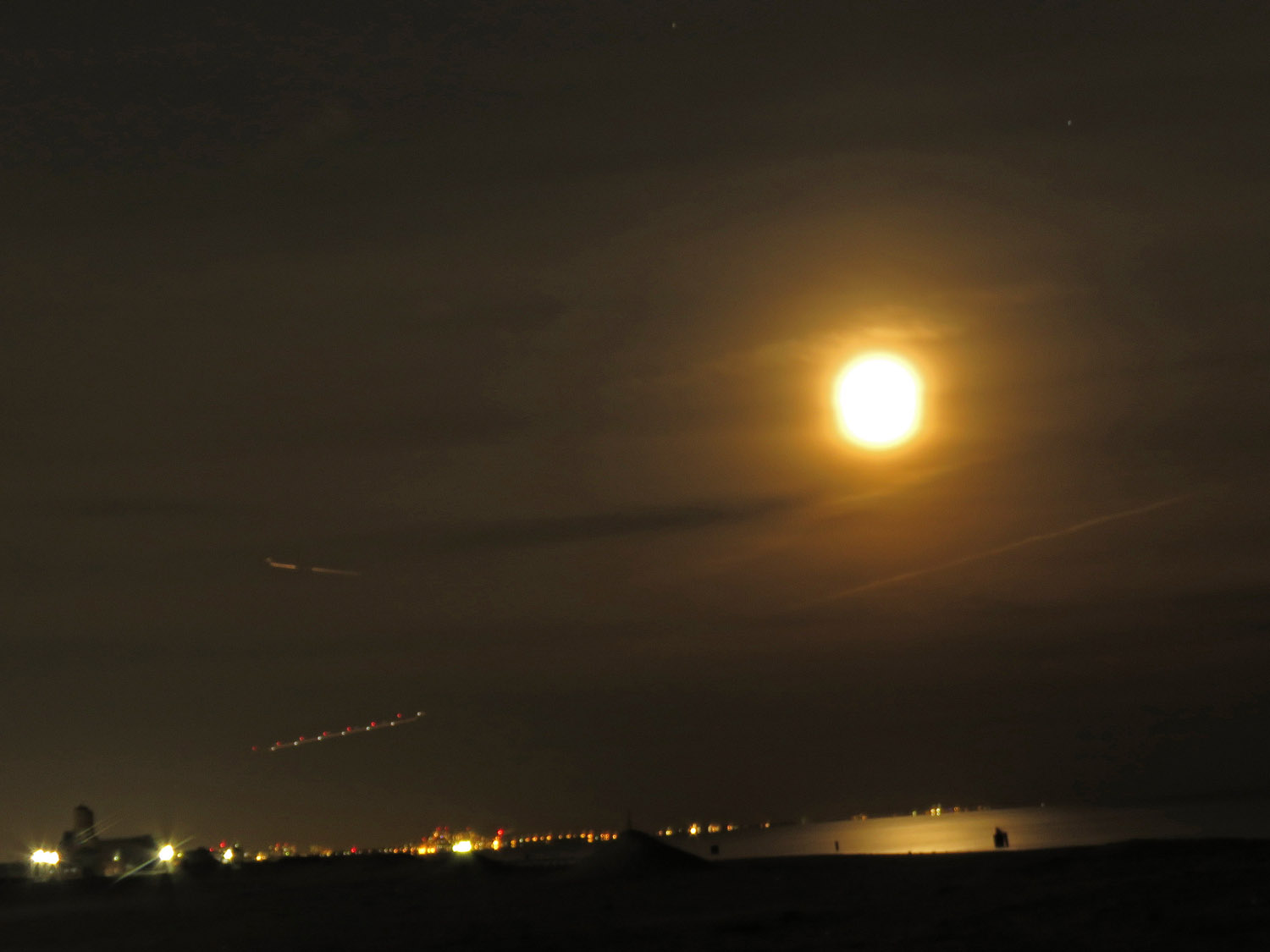 Time-lapse (8 seconds) photo of supermoon with lights of planes landing at Kennedy Airport.