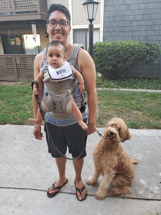Parent wearing baby walking dog Costa Mesa doula