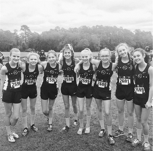 Before the start of the USATF National Junior Olympic Race in Tallahassee, Florida on December, 9, Whisper Runners, Kira, Abby, Ashley, Kiley, Katelyn, Emily, Callie, and Candice pose for a timeless photo.