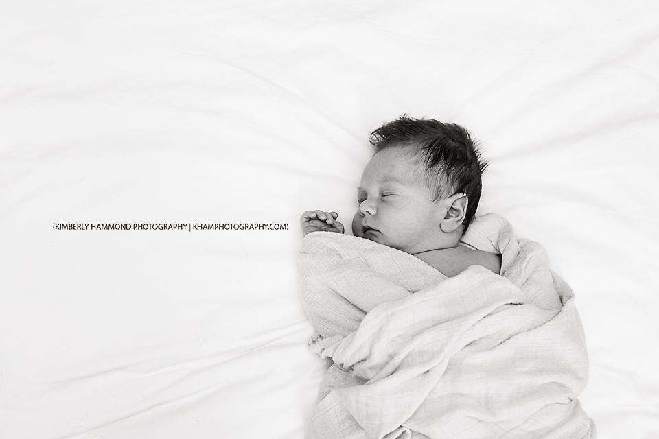 Baby sleeps swaddled on bed during newborn lifestyle session in Fort Worth, TX.