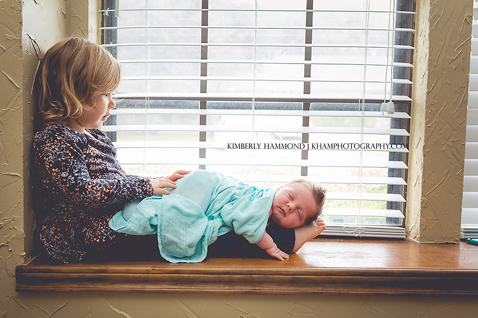 Big sister holds little brother during newborn lifestyle session in Fort Worth, TX.