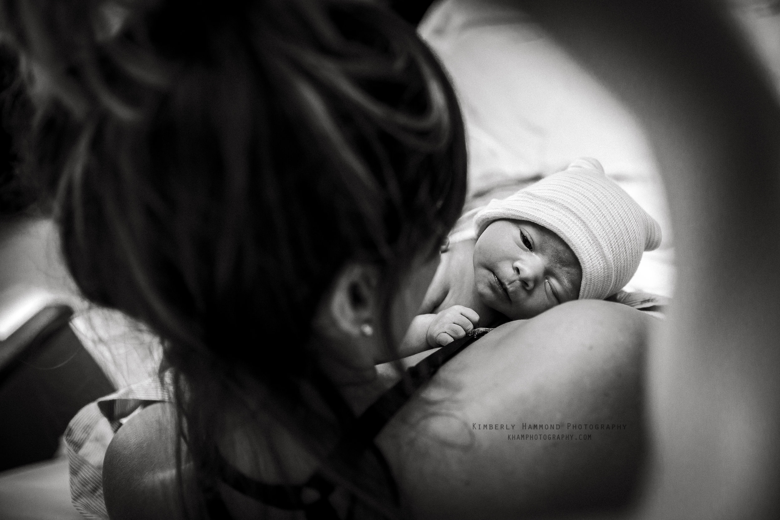 Baby stares at mom during Fresh 48 session at Mansfield Methodist in Mansfield, TX.