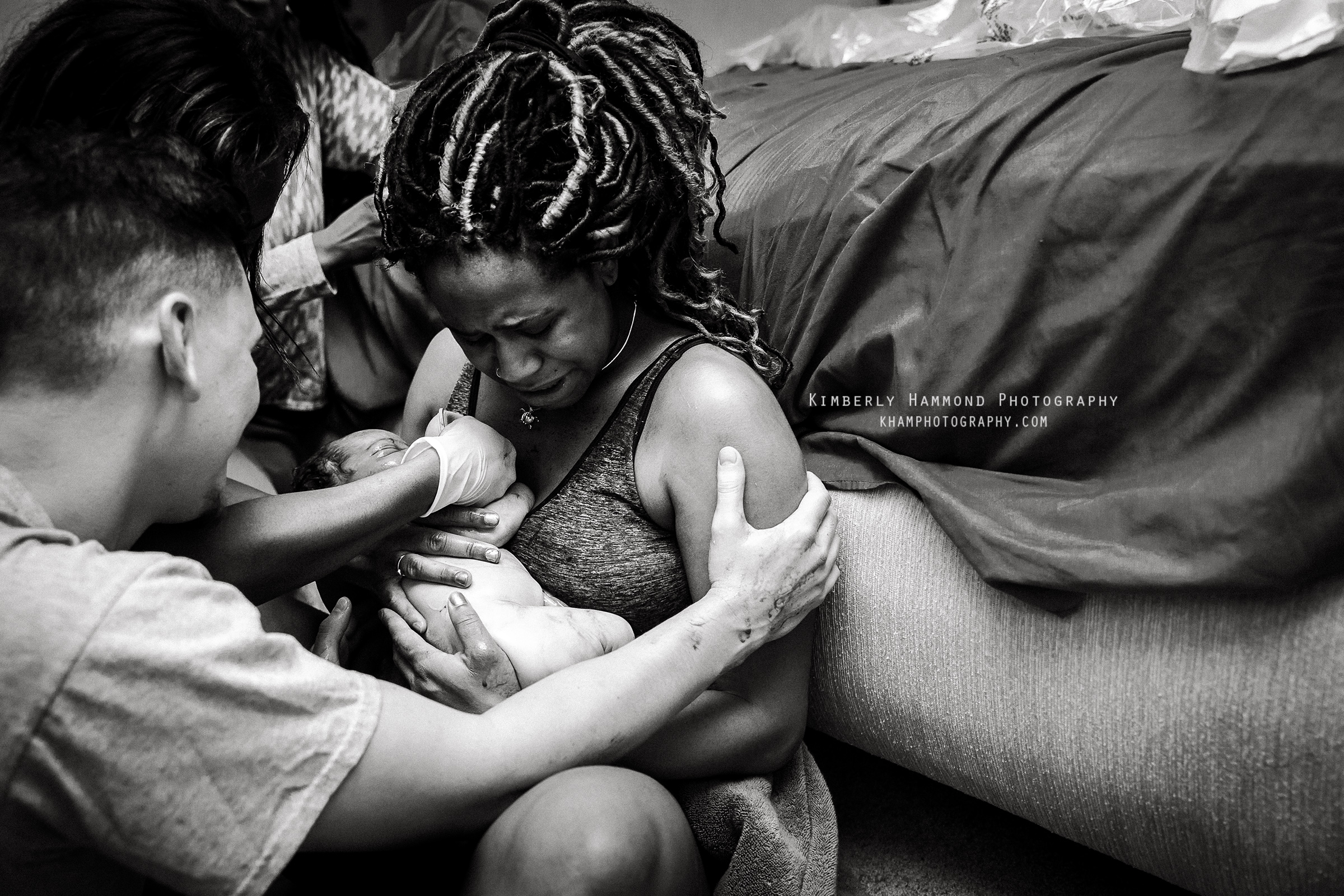 Dad excitedly embraces mom after their baby was born at their homebirth in Fort Worth, TX.