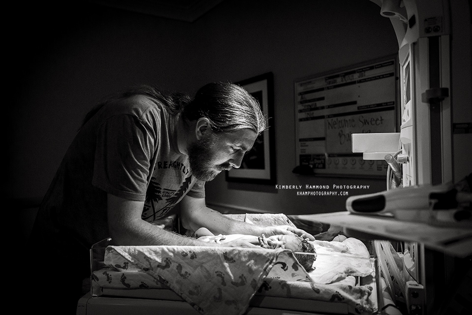 Dad cradles son in warmer after natural hospital birth at Harris Methodist in Fort Worth, TX.