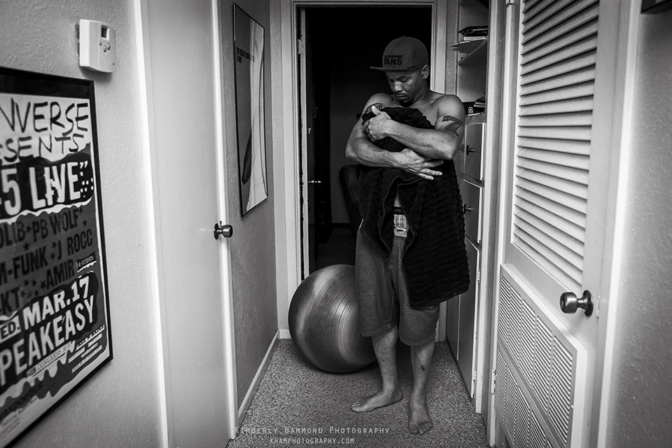 New dad walking new baby around their home during homebirth in Fort Worth, TX.
