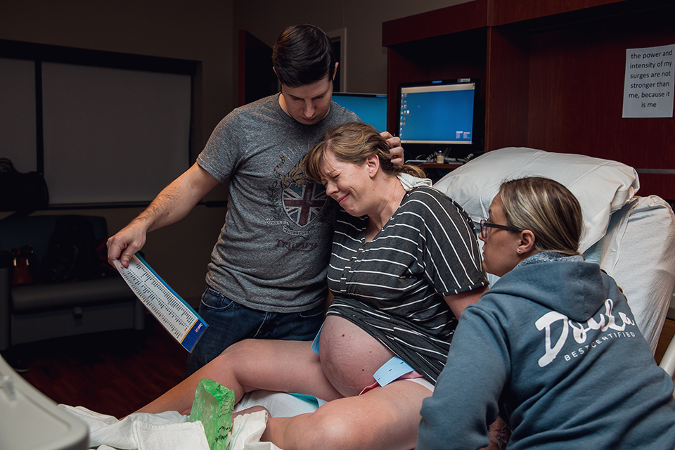 Husband and doula help laboring mom through contractions during natural hospital birth in Grapevine, TX. DFW Birth photography| Dallas Fort Worth Birth Photographer