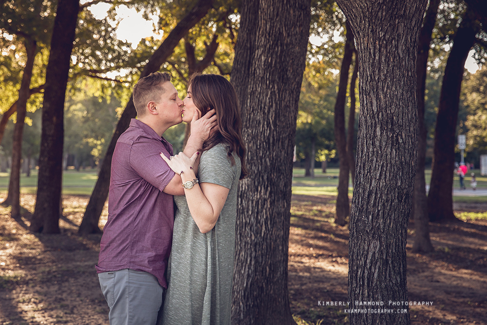 Man and woman kiss during their engagement photography session at Trinity Park in Fort Worth, TX.