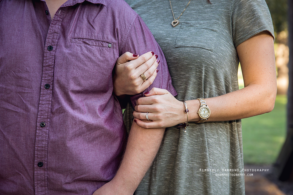 Woman braces mans arm during their engagement photography session at Trinity Park in Fort Worth, TX.