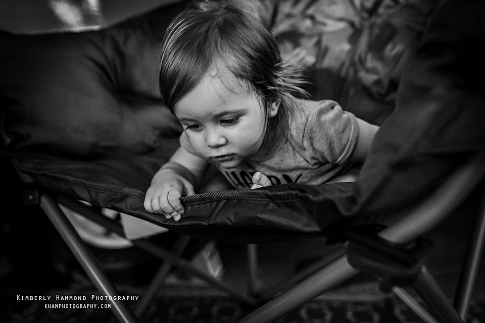 One year old peers over chair while camping in Grand Prairie TX.