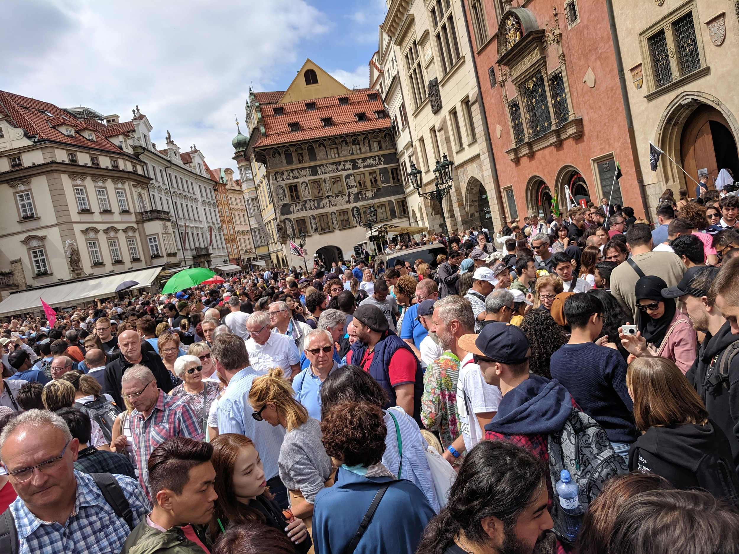 Tourists crowd Prague Old Town streets.