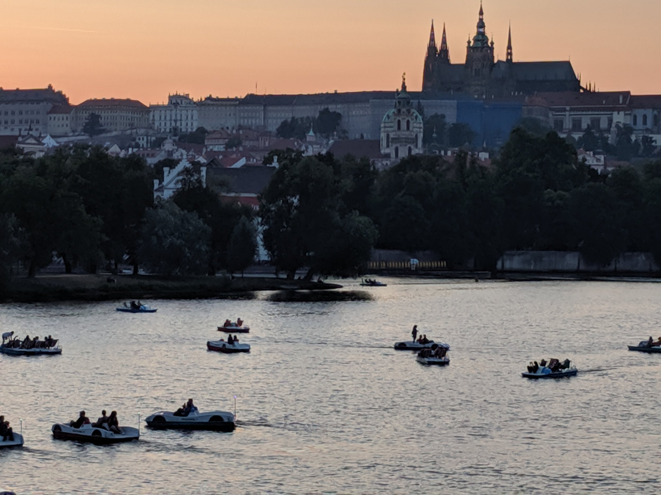 Paddle boats at dusk before Prague Castle and Cathedral.