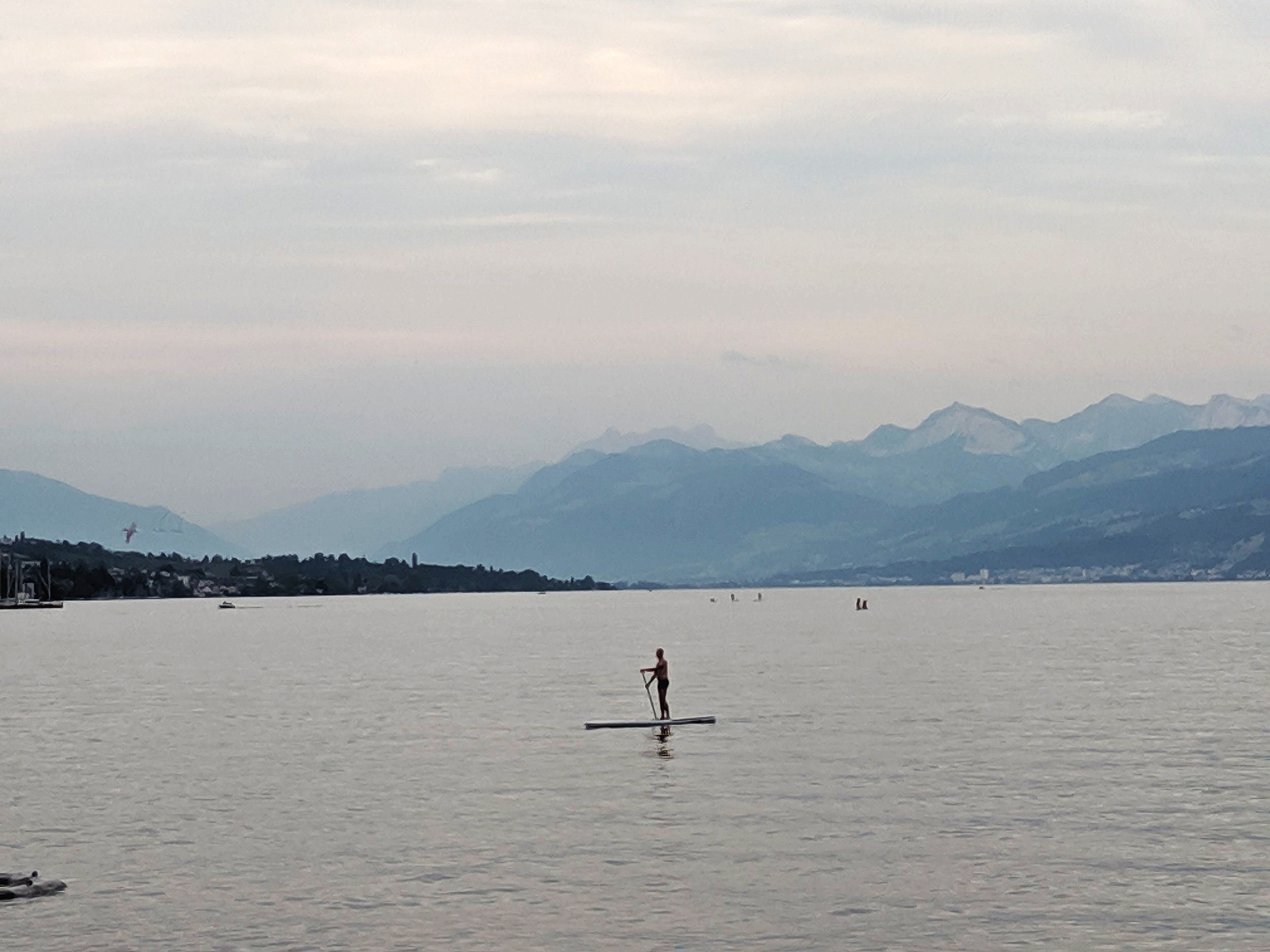 A paddle boarder makes his way across Lake Zurich at dusk — several boys were swimming by the shore. Can you spot snow capped peaks in the distance?