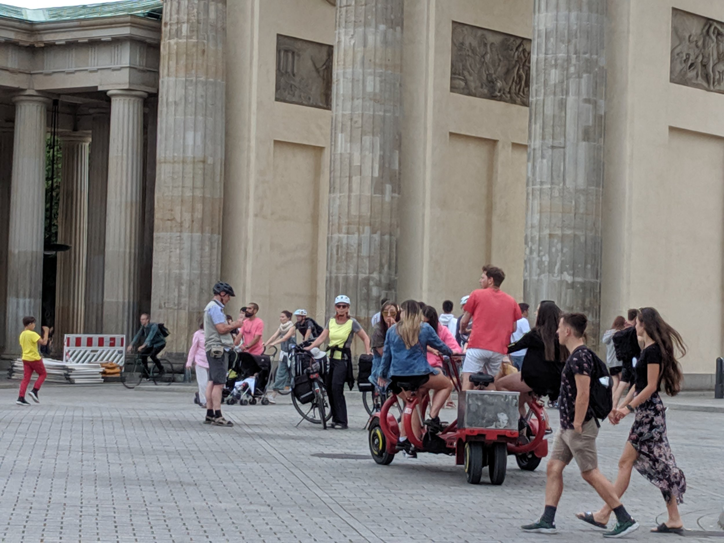 A spirit of freedom is felt throughout Berlin: here at the Brandenburg gate tourists have fun with all manner of transportation. Later in the day a band set up a stage for a free public performance. The city is both security conscious and freedom loving.