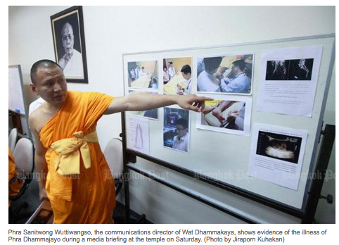 Ven. Pasura rather than Ven. Sanitwong as incorrectly attributioned by the Bangkok Post, points to a photo of MV Dhammajayo's leg at the press conference.