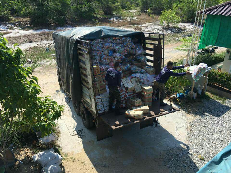Military personnel unloading dry foods at Narathiwat Youth Training Center.