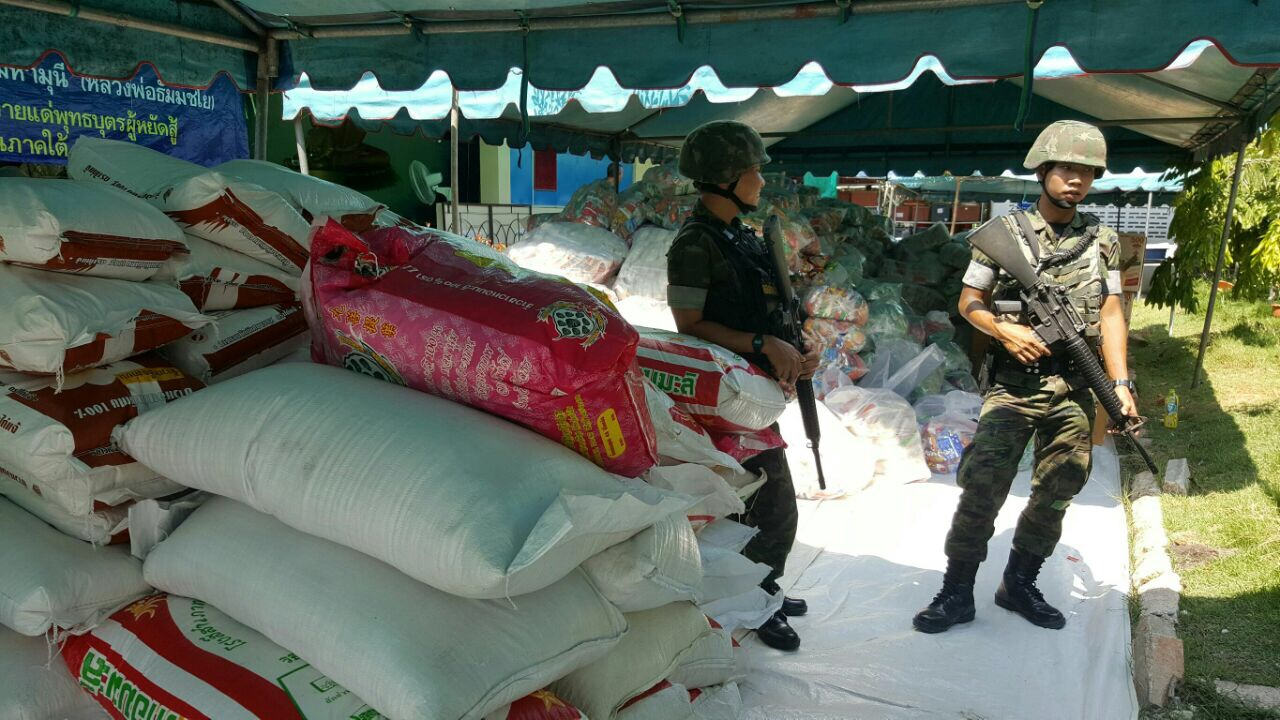 Soldiers provide safety to those delivering and receiving the food that has been sent as aid for the Southern Thailand Region.