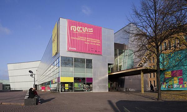 Nykytaiteen museo Kiasman ARS11-näyttelyssä yhdistettiin kuvailutulkkaus museo-opastukseen. Kuvassa ulkoapäin Kiasman sisäänkäynti ja seinälle ripustettu suuri ARS11-mainos. Kuva: Kansallisgalleria / Pirje Mykkänen.