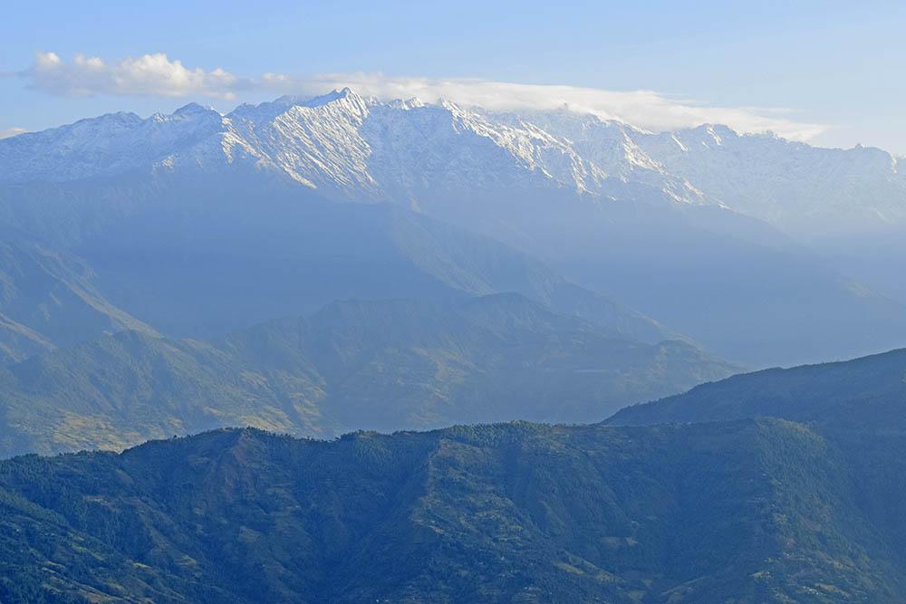 Etäisyys tuo työhön uusia näkökulmia.  Kuvassa on henkeäsalpaavan avara maisema Himalajan vuoristosta Nepalissa. Nouseva aurinko hivelee kaikkein korkeimpia ja kauimmaisia lumihuippuja. Lähempänä matalammat metsäiset vuoret ovat vielä varjossa ja sinertävän usvan peitossa.