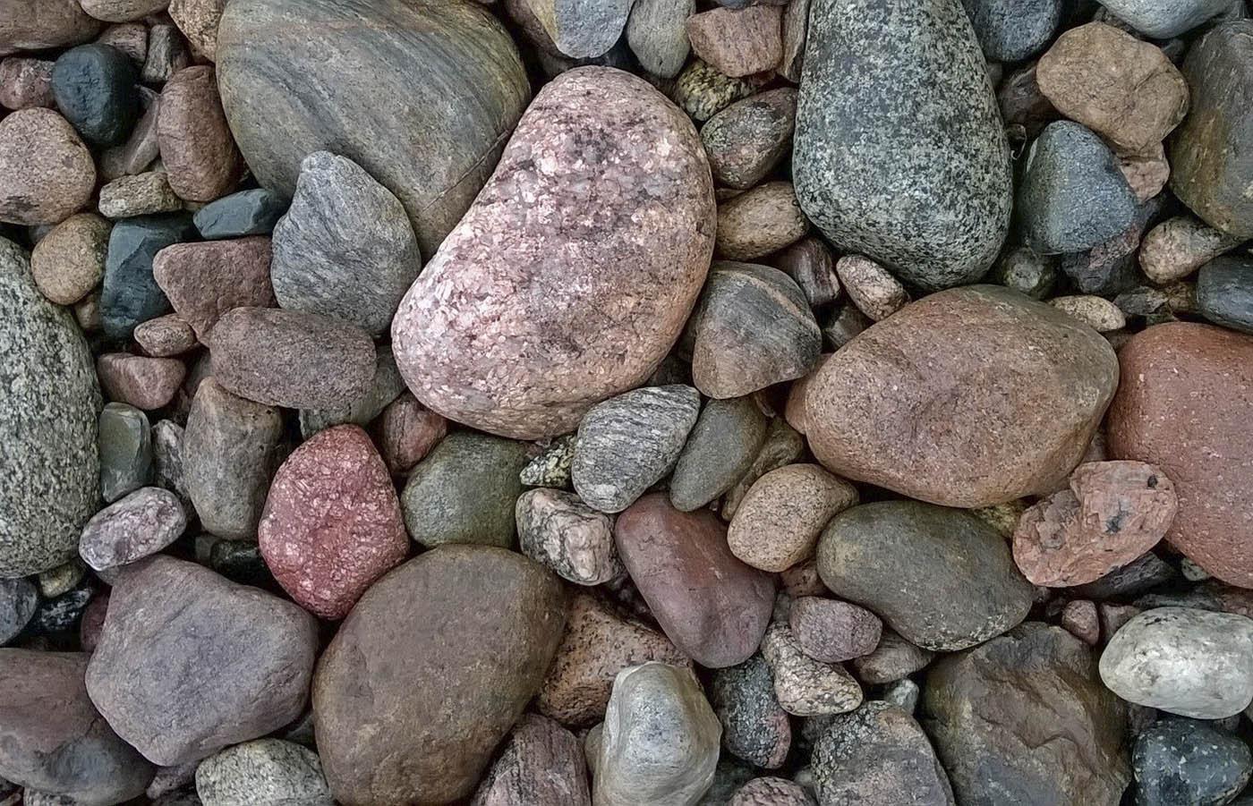 Kuvassa on rantakivikko, pirunpelto, jossa on monenkokoisia punertavia, harmaita, mustia, raidallisia ja täplikkäitä sateen liukastamia kivenmurikoita.