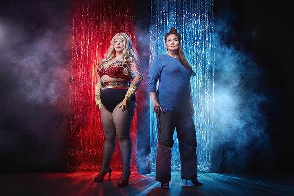 Kuvassa burleskitaiteilija Bettie Blackheart ja ohjaaja Iina Terho seisovat esiintymislavalla poseeraten ylväänä välkehtivän kimalleverhon edessä. Kuva: Timo Luomanen