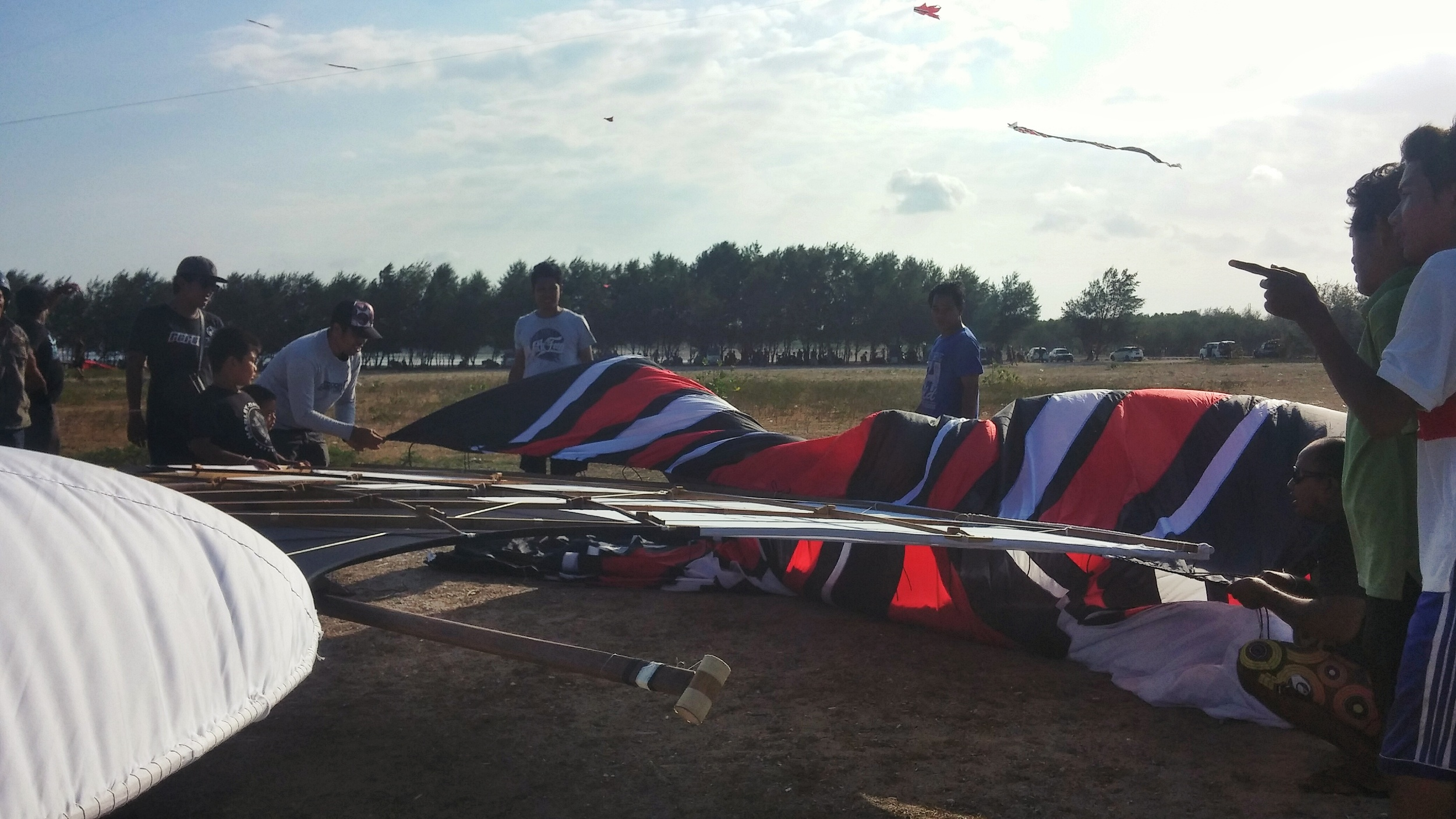 The team starts tying on the tail of the kite.