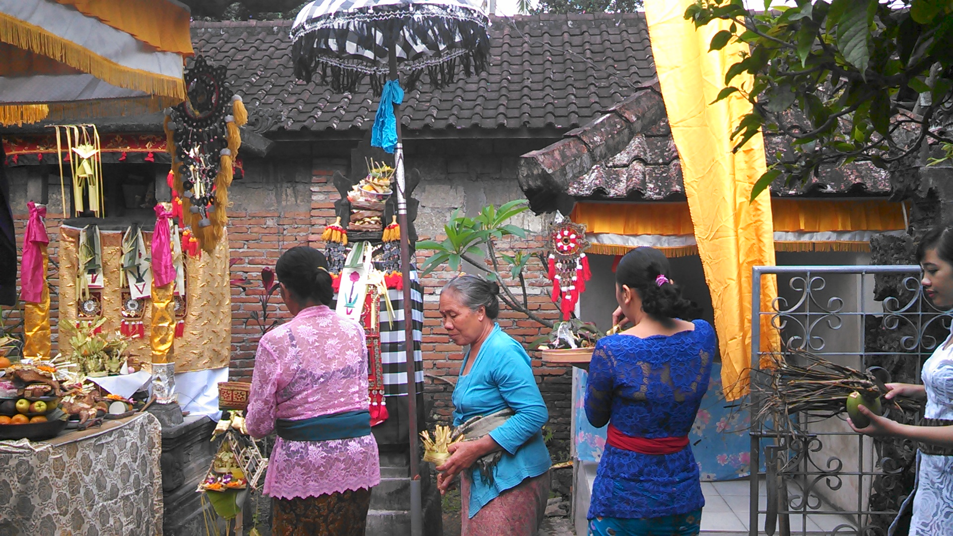 The women are still bringing in more and more offerings for the ceremony in the family temple.
