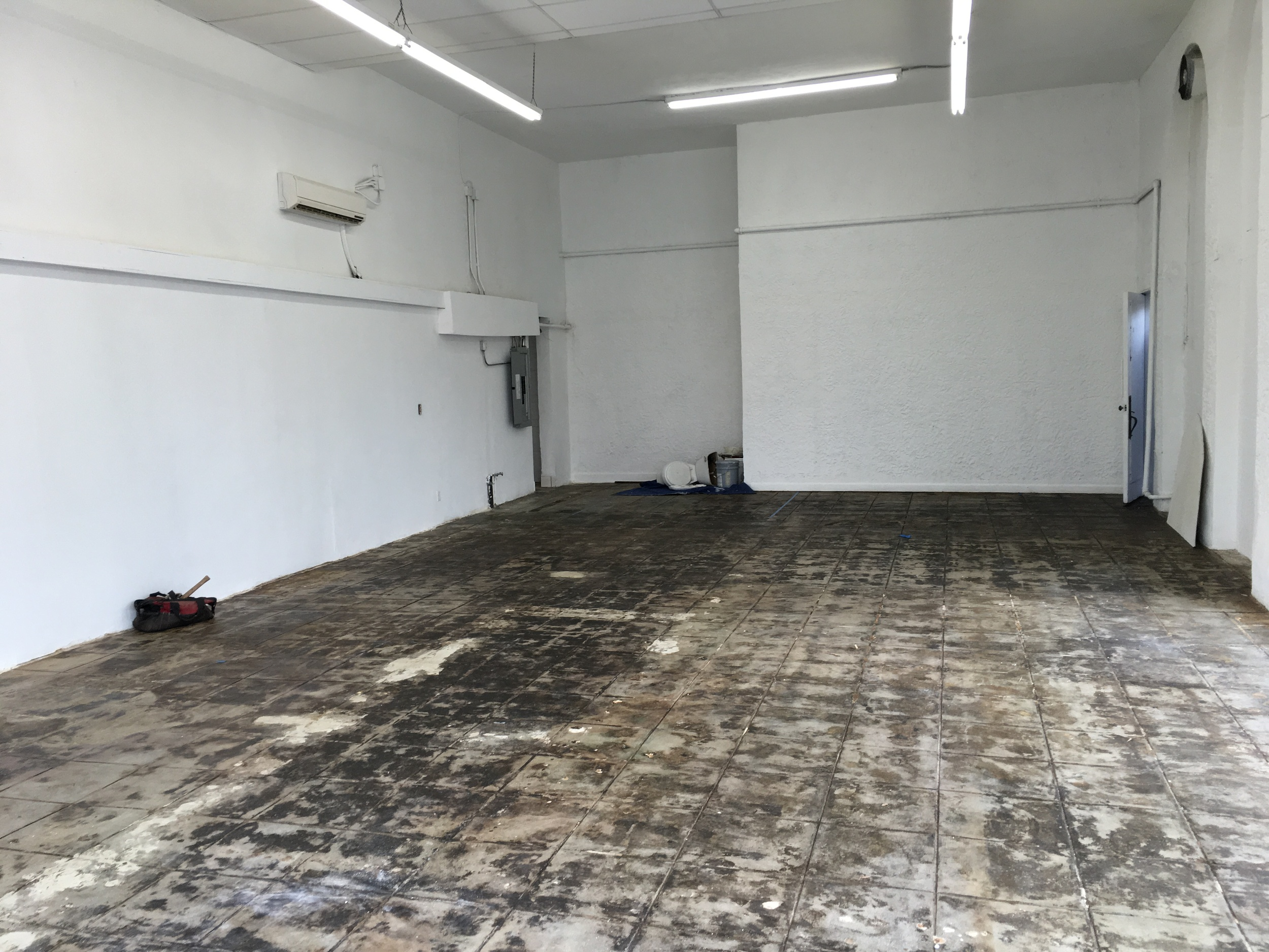 Concrete floor is scraped, sanded and sealed.