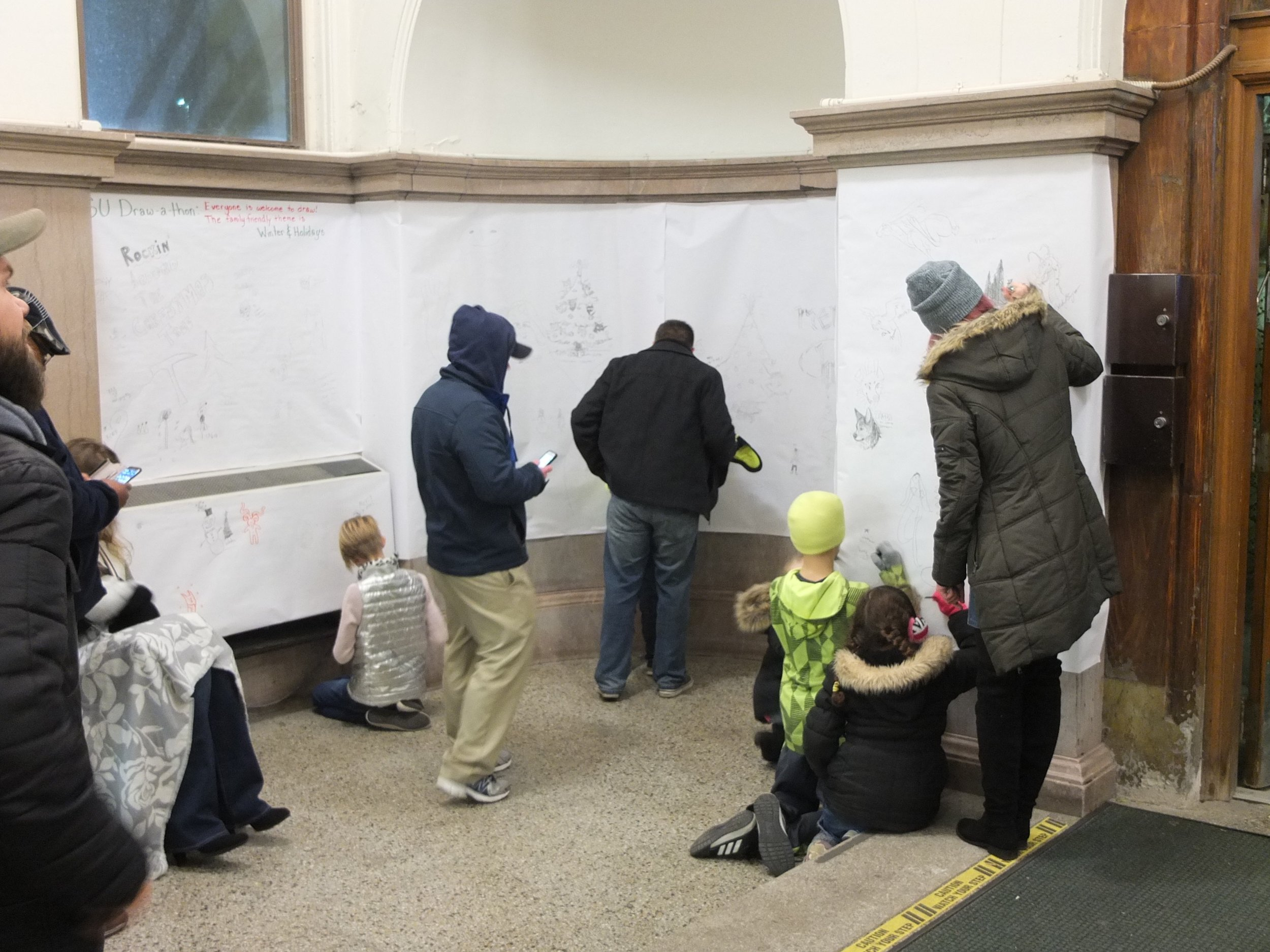"In 2017, with the help of my drawing students, we developed and hosted the WSU Draw-A-thon as part of the 45th Annual Noel Night Celebration in Midtown Detroit. The students came up with the theme of ""Winter & Holidays."" Hundreds of people from the community came out and participated by drawing on the walls of the historic Old Main building on WSU's campus."