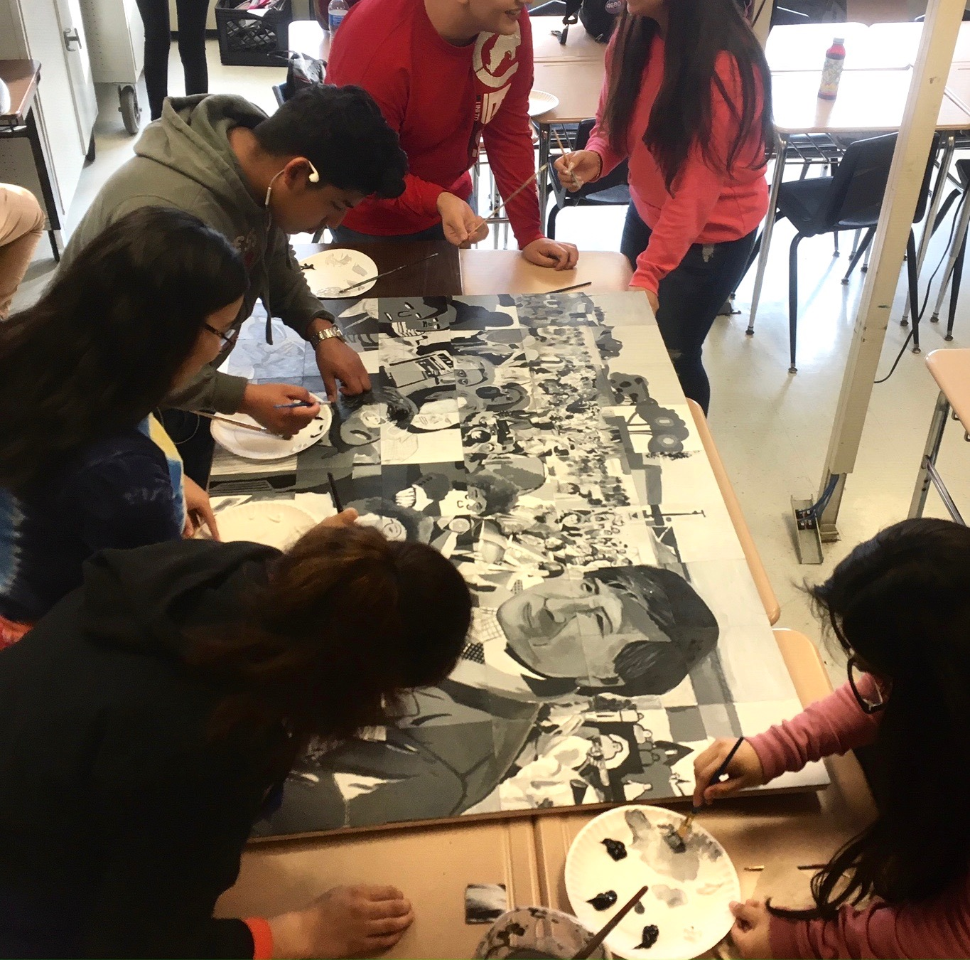 High school students put the finishing touches on a class mural for Cesar Chavez Day of Service.