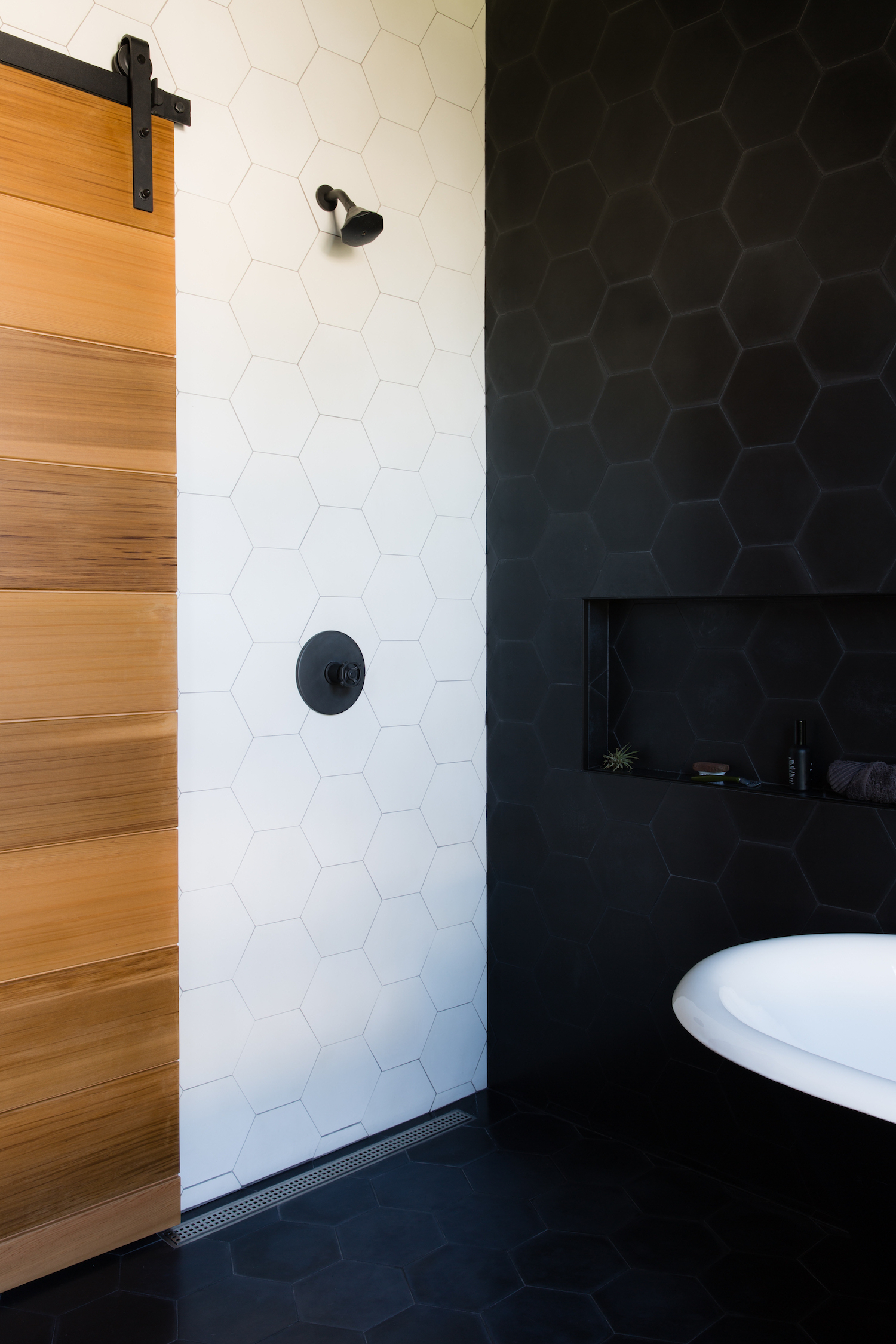 bathroom with black and white hexagonal tile walls and black shower fixtures and wood barn door and soaking tub.jpg