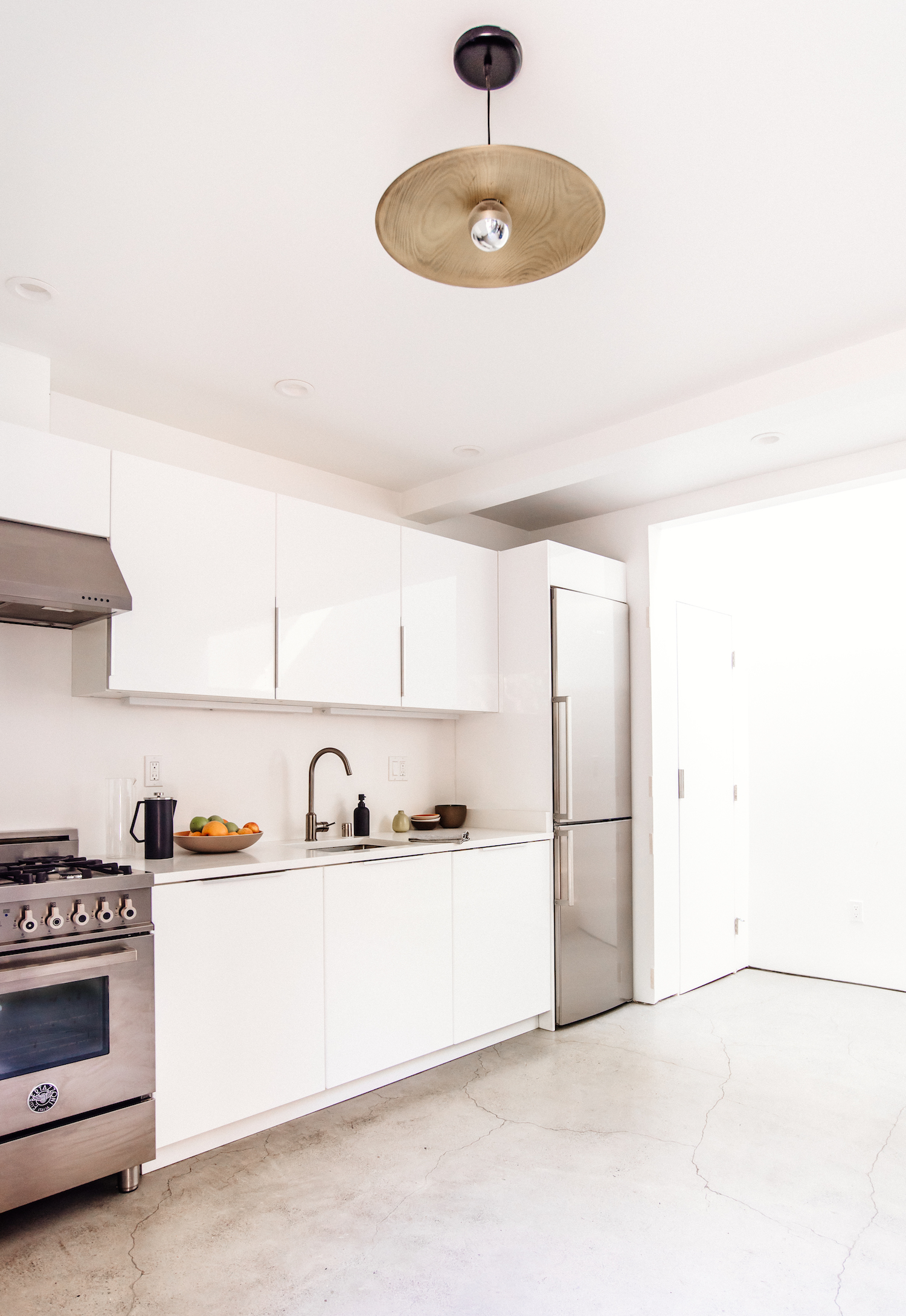 kitchen with cement floors and white cabinets and white marble counters and stainless steel appliances.jpg