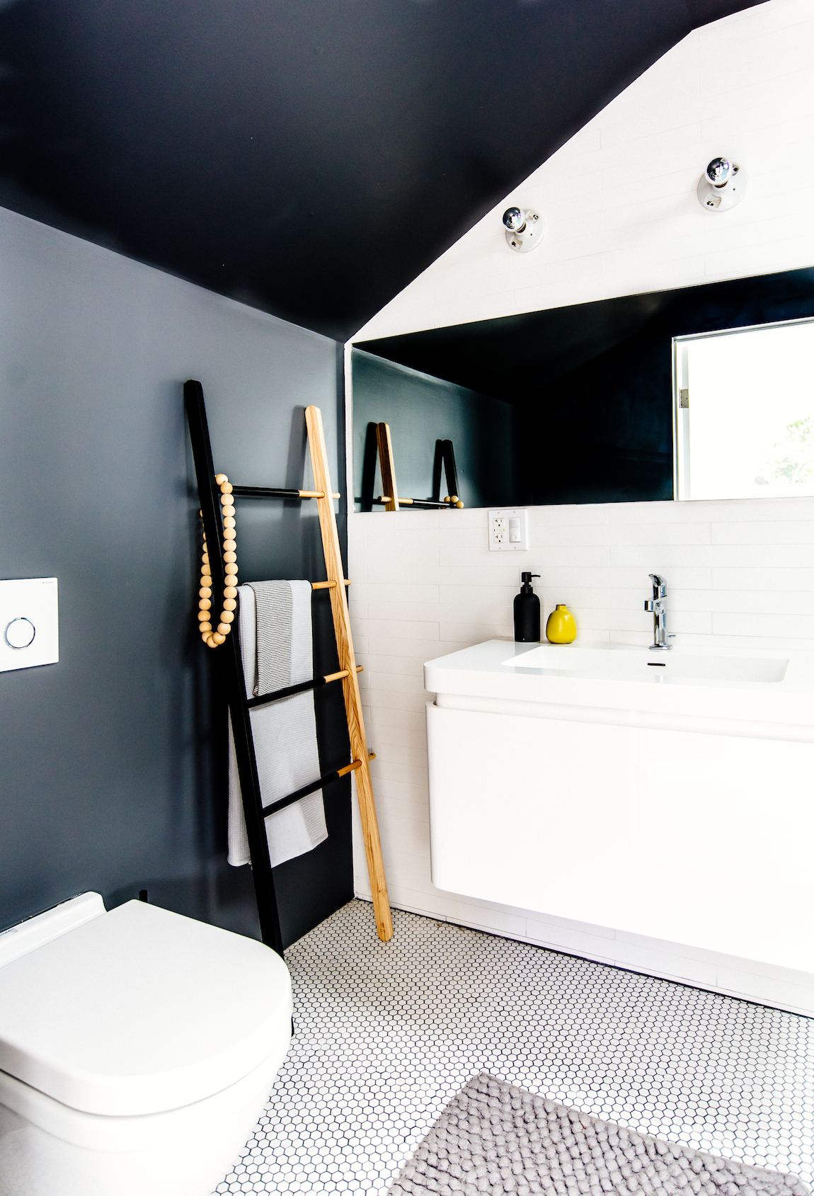 bathroom with hexagonal floor tile and white floating vanity and floor mounted toilet and leaning towel rack and chrome fixtures.jpg