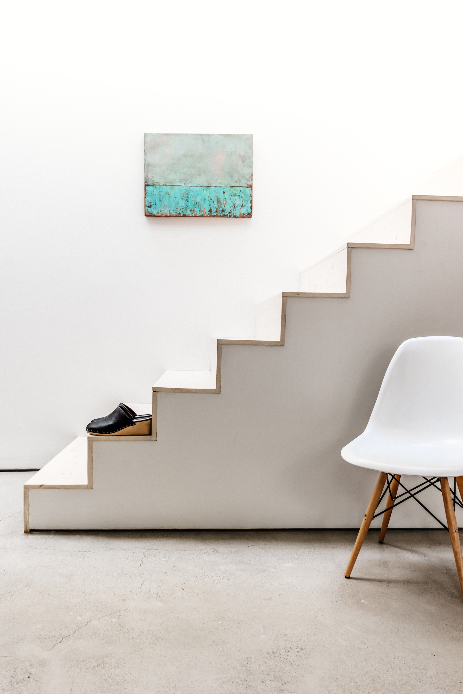 open staircase with light wood steps and cement flooring and white accent chair.jpg