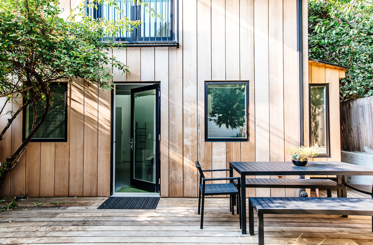 cottage entry with wood paneled facade and black trimmed windows and doors and patio with black furniture.jpg