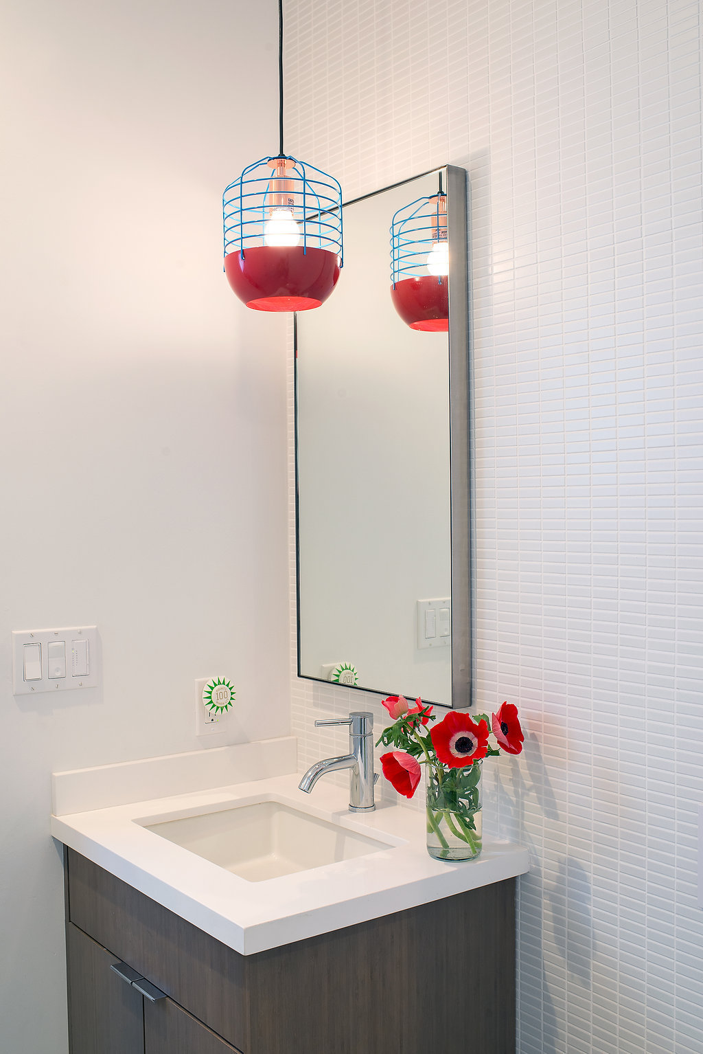 bathroom with wood vanity and white counters and red and blue pendant light and white wall taile and chrome fixtures.jpg