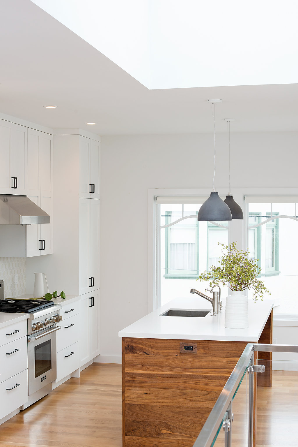 kitchen with white cabinets and wood island and white marble counters and stainless steel appliances and pendant lighting.jpg