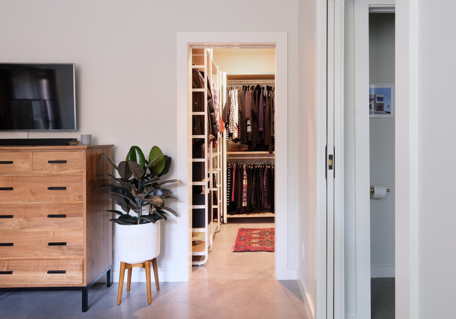 master bedroom and closet with wood furniture and cement floors.jpg