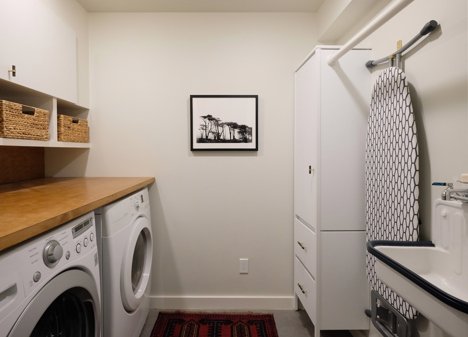 laundry room with custom wood counter and white cabinets.jpg