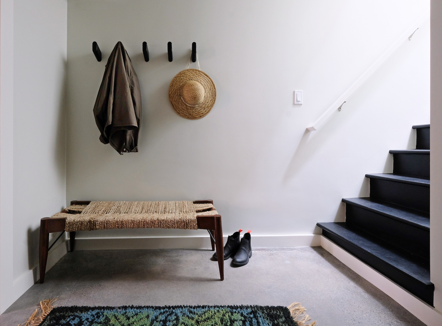 entry area with woven bench and cement floors and black staircase.jpg
