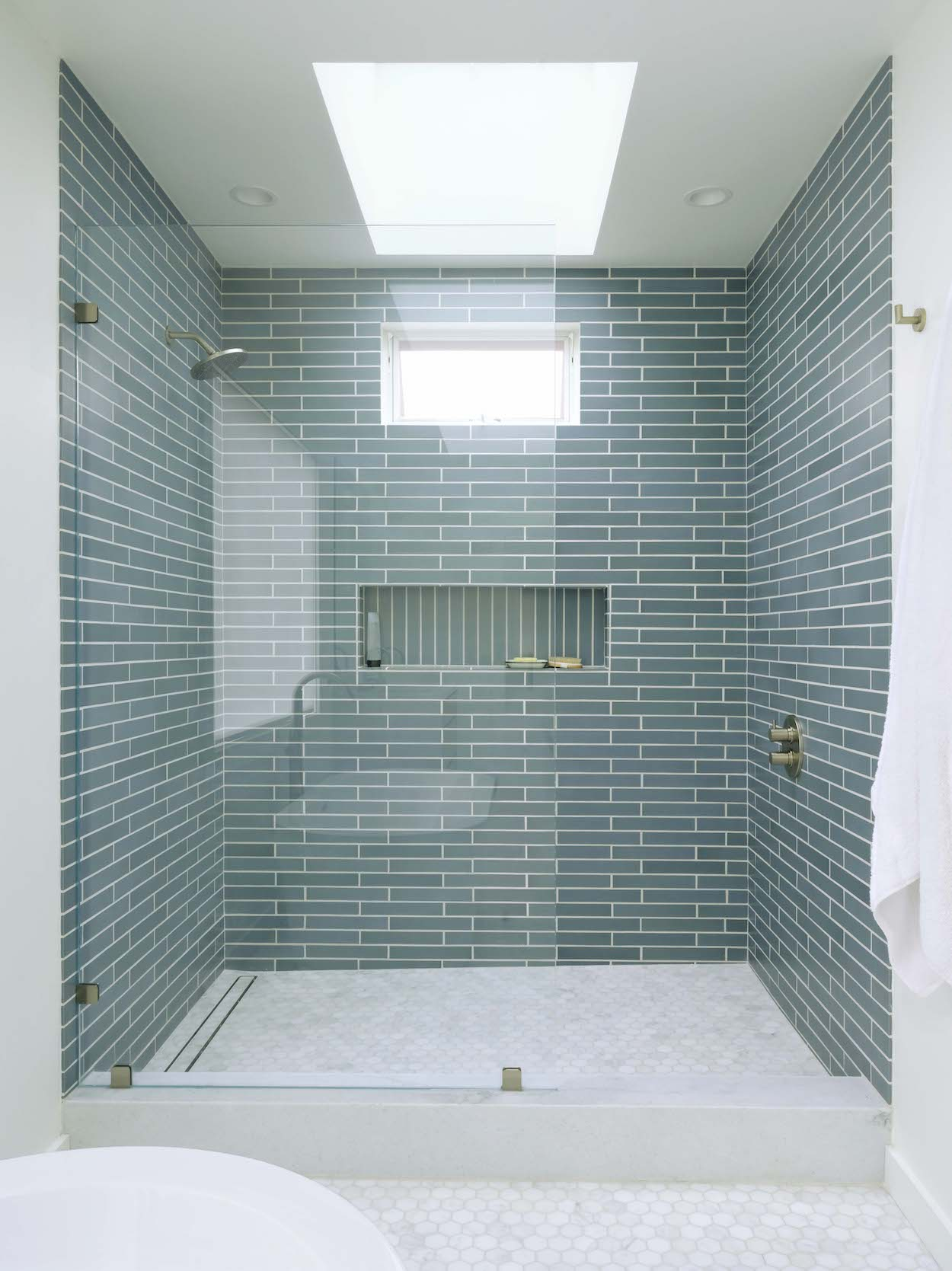 walk in shower with marble flooring and blue wall tile with vertical tiled niche and brushed nickel shower fixtures.jpg