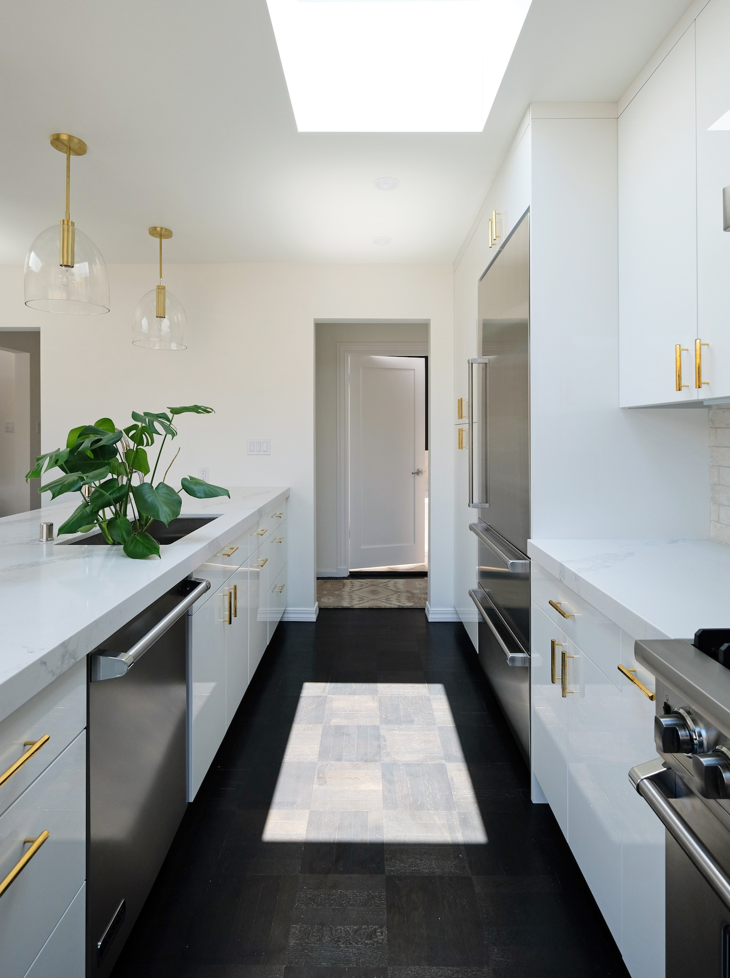 kitchen with white cabinets and gold hardware and gold pendant lighting and stainless steel appliances and wood flooring and white marble counters.jpg