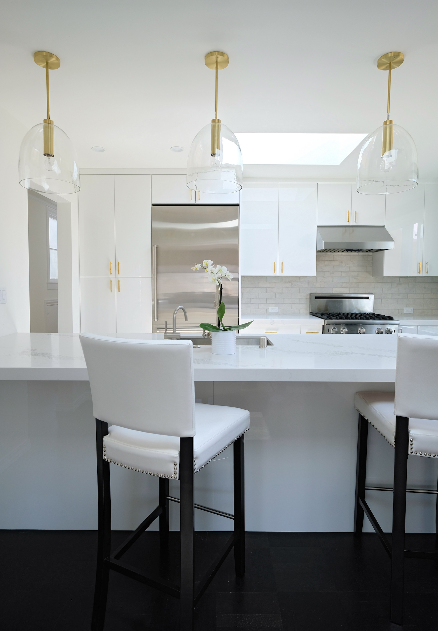 white kitchen with white marble counters and bar seating and gold accents.jpg