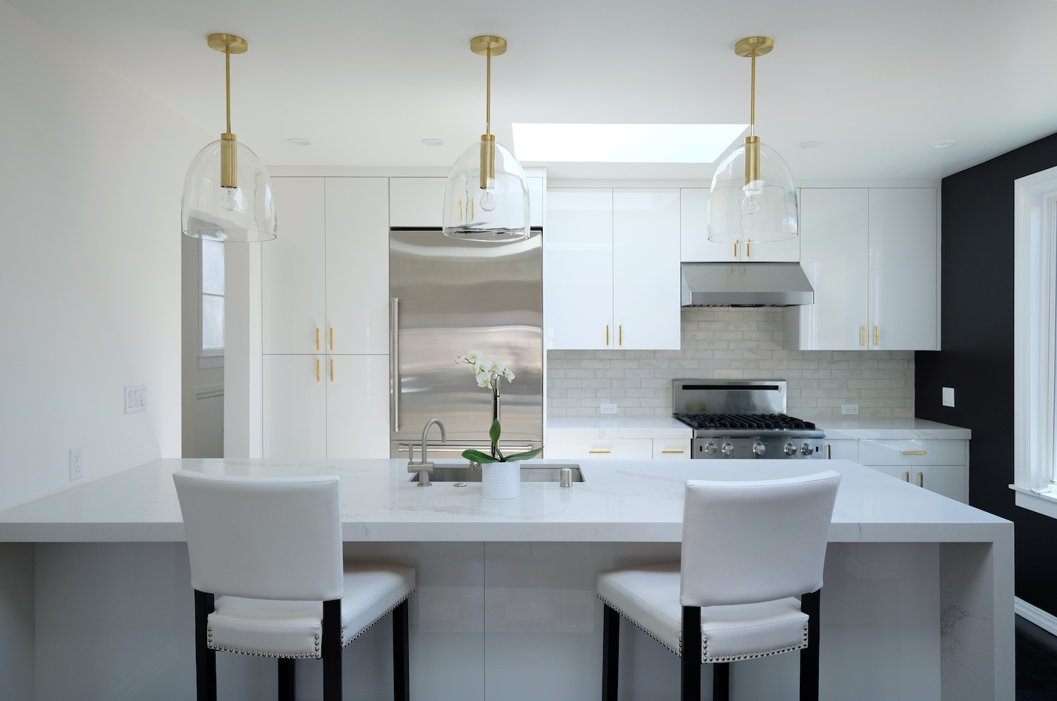 white kitchen with white marble counters and gold pendant lighting and black and white walls.jpg